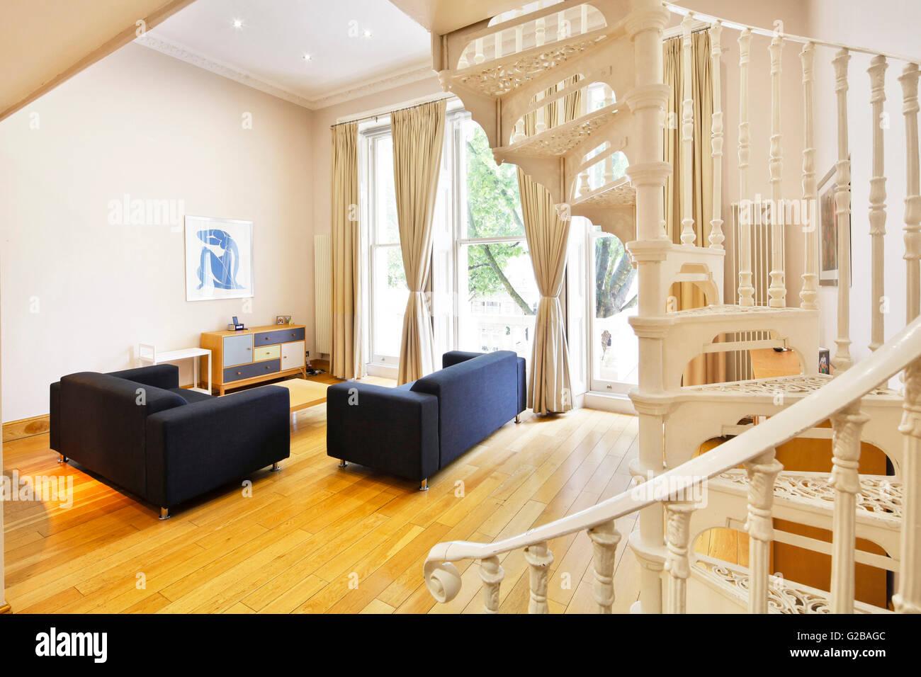 Inverness Terrace. Spazioso soggiorno con grandi finestre. White scala a spirale parzialmente a vista. Immagini Stock