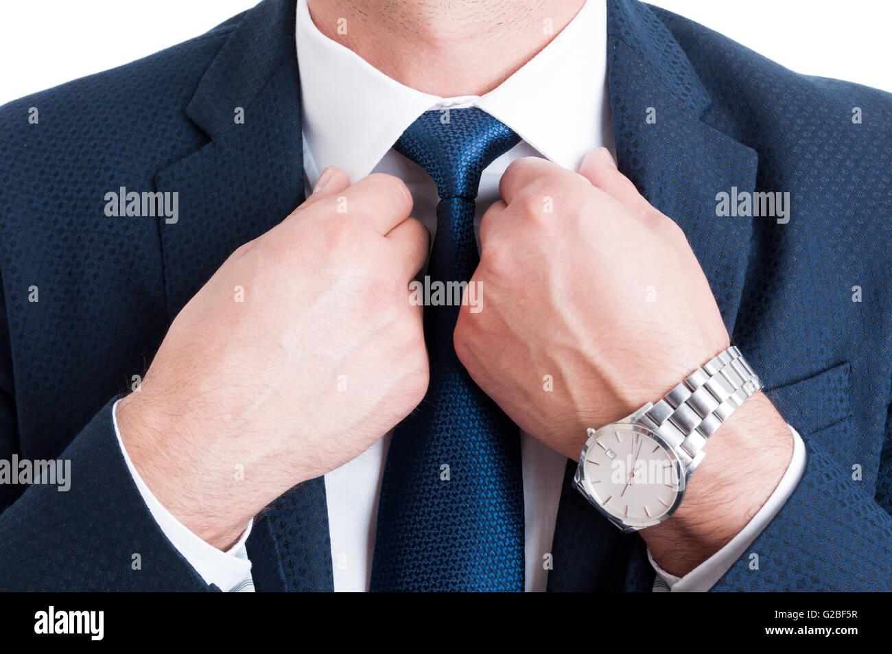 Primo piano con imprenditore cravatta fissaggio collare bianco e indossando elegante orologio da polso Immagini Stock