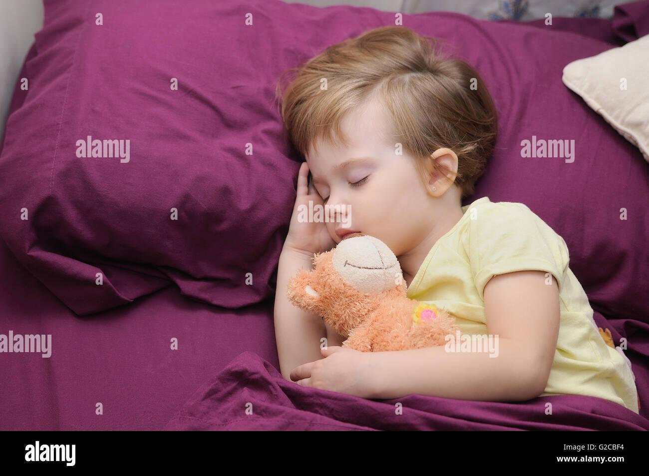 Ragazza dorme pacificamente con il suo orsacchiotto tra fogli di granati Immagini Stock