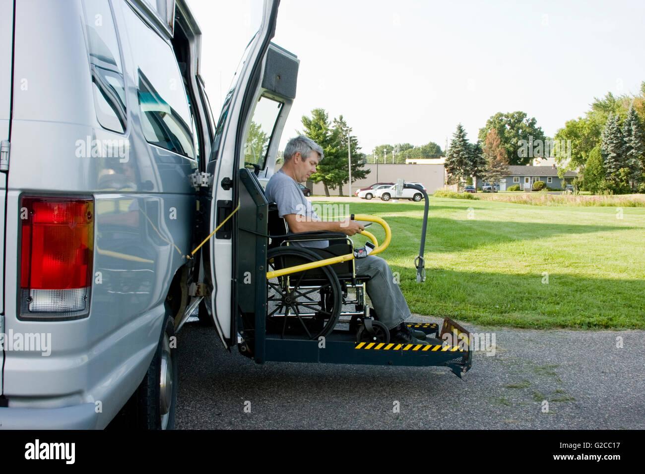 Conversione di disabilità sollevare van con un uomo su una sedia a rotelle sul gate Immagini Stock