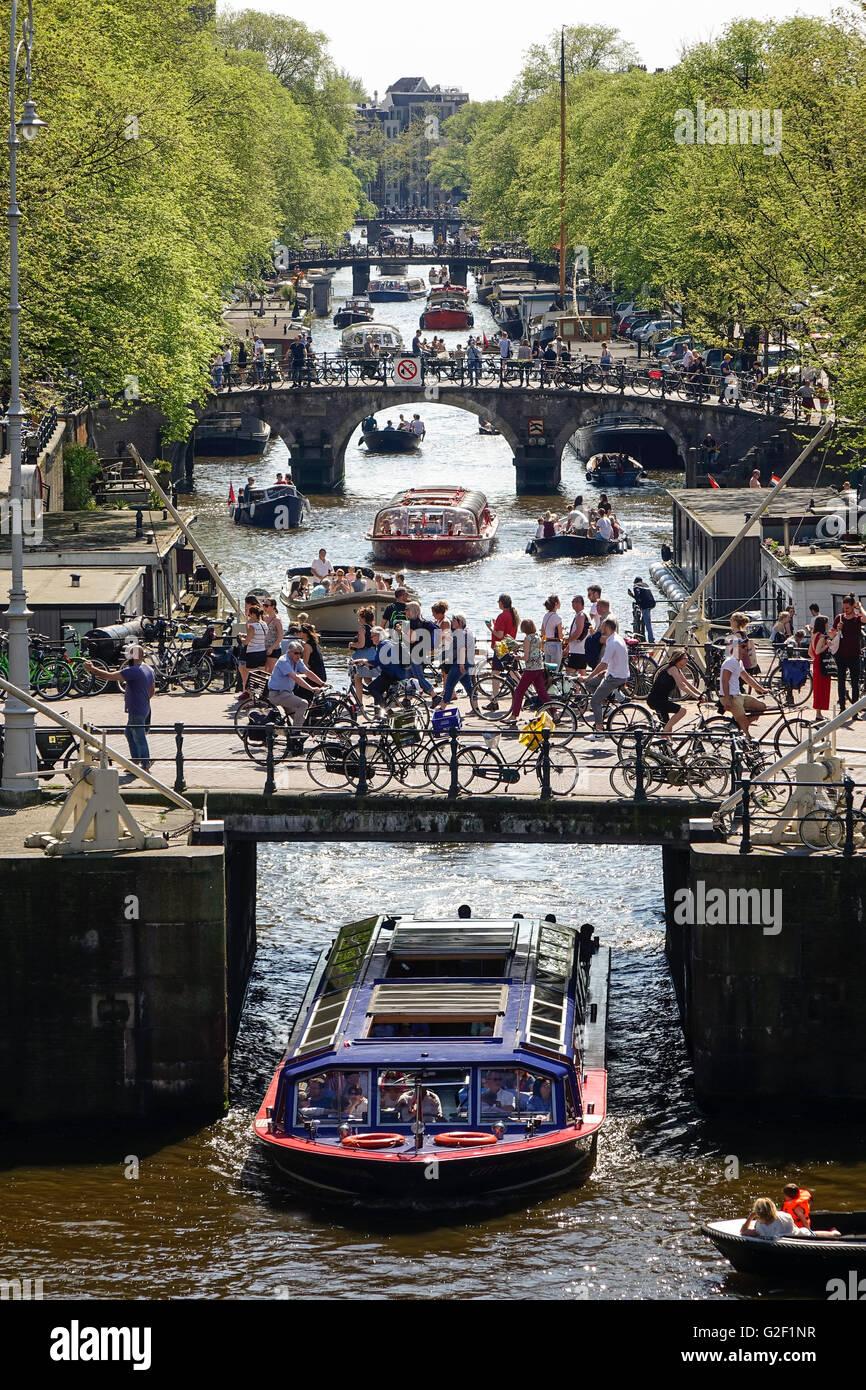 Canali di Amsterdam. Quattro ponti con molti ciclisti sul canale Prinsengracht con canal tour barche e piccole imbarcazioni Immagini Stock