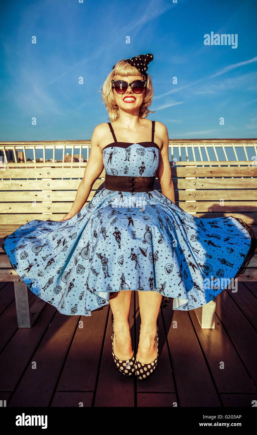 Giovane donna adulta in abito retrò e tacchi alti e seduto sul Boardwalk banco a spiaggia Immagini Stock