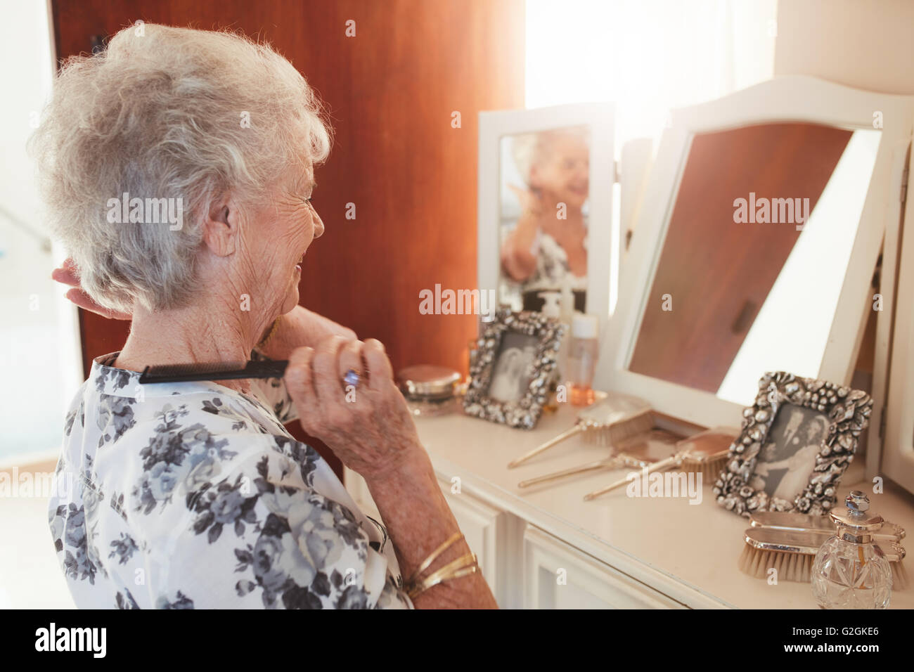 Felice donna senior pettinare i capelli a cassettiera in casa. Femmina anziani preparano davanti a uno specchio Immagini Stock
