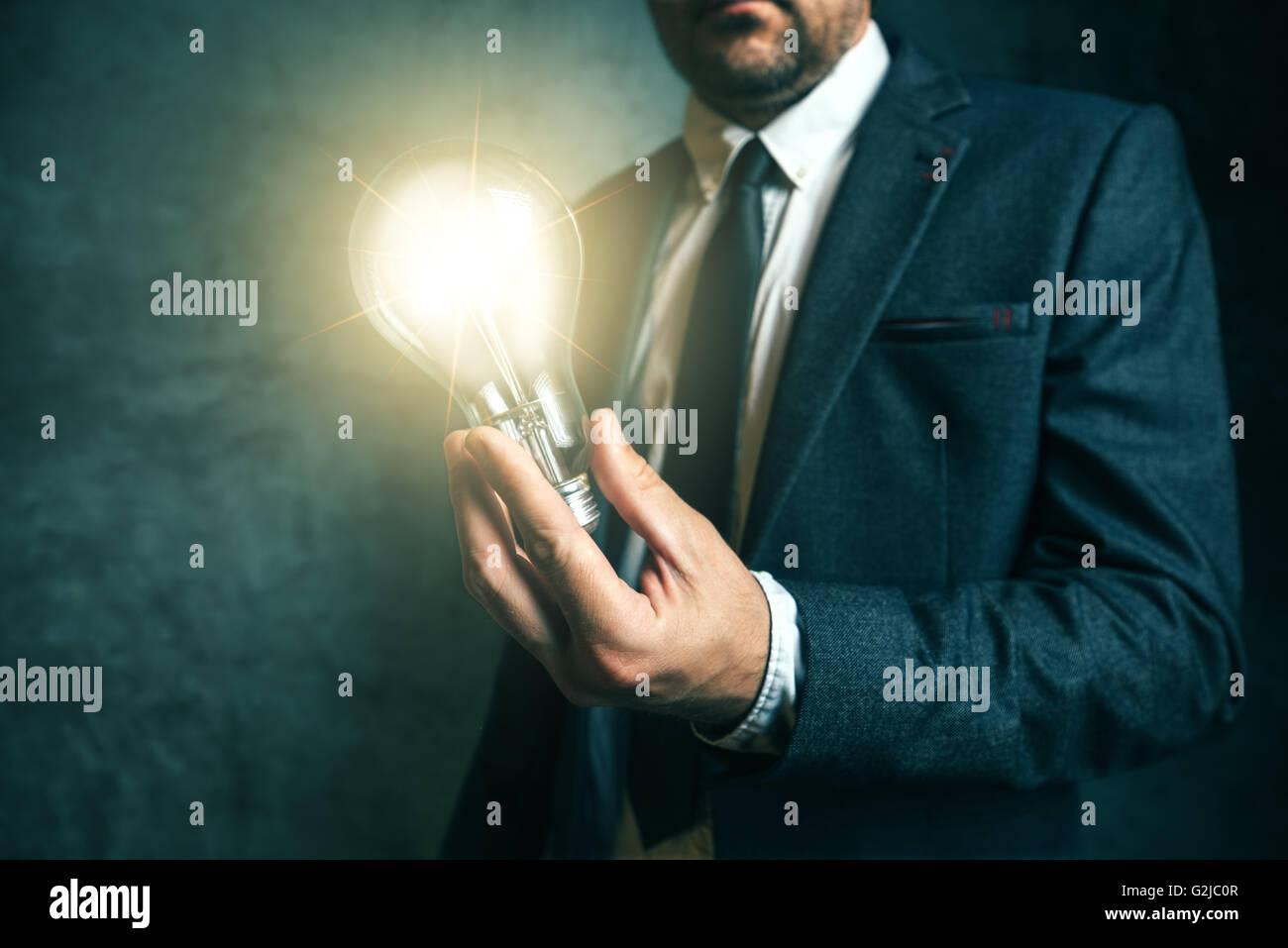 La creatività imprenditoriale e il concetto di visione con elegante imprenditore adulti azienda brillante lampadina Immagini Stock