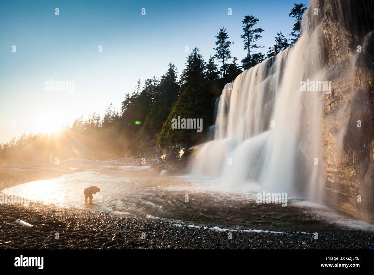 Escursionista faccia il lavaggio, Tsusiat cade, campeggio, West Coast Trail, Pacific Rim Parco nazionale di riserva, Immagini Stock