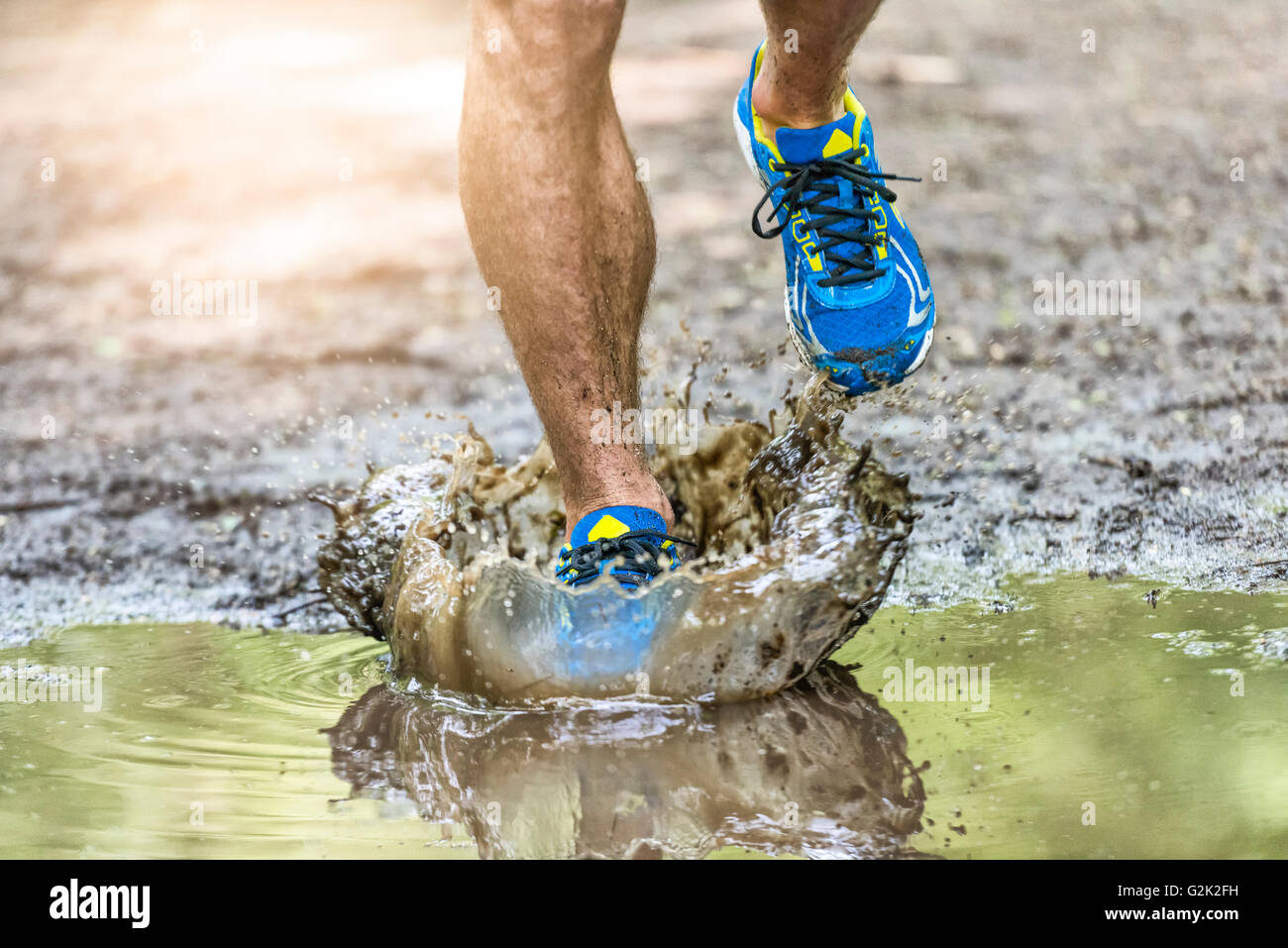In funzione uomo a camminare in una pozza, schizzi le sue scarpe. Cross country trail. Azione di congelamento Immagini Stock