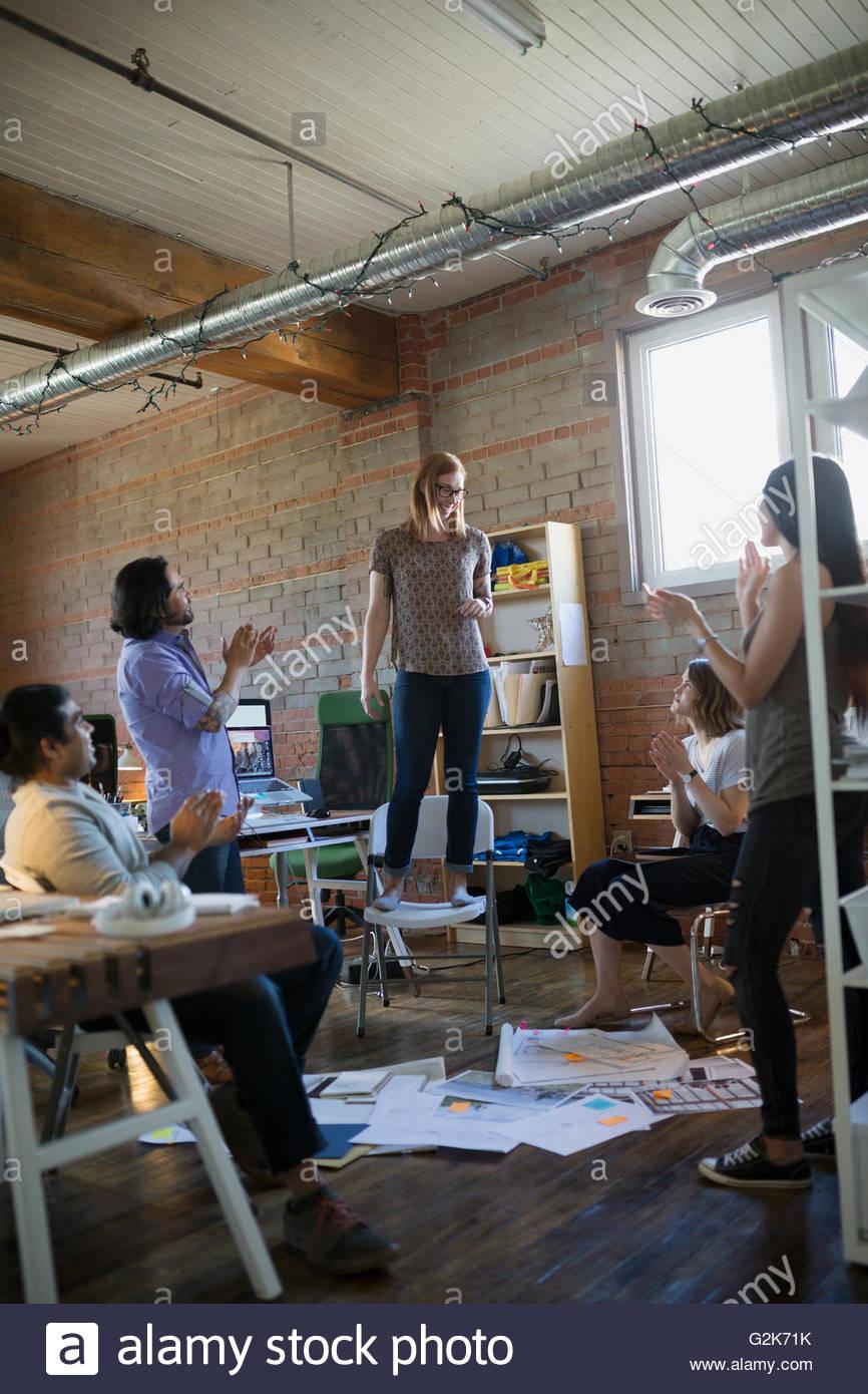 I colleghi battimani per designer permanente sulla sedia in ufficio Foto Stock