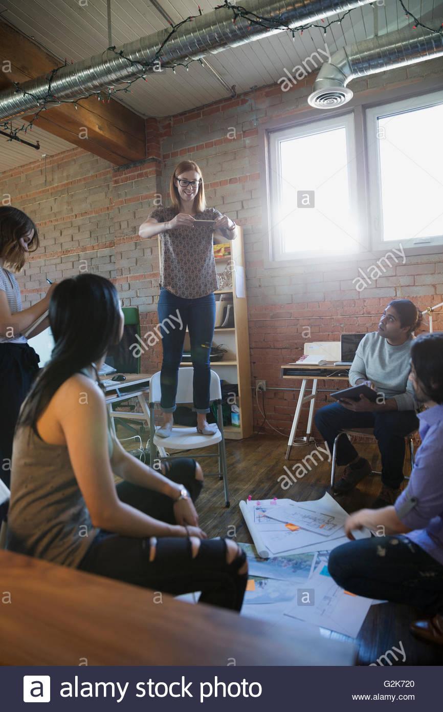 Designer in piedi sulla sedia a fotografare le prove su pavimento per ufficio Immagini Stock