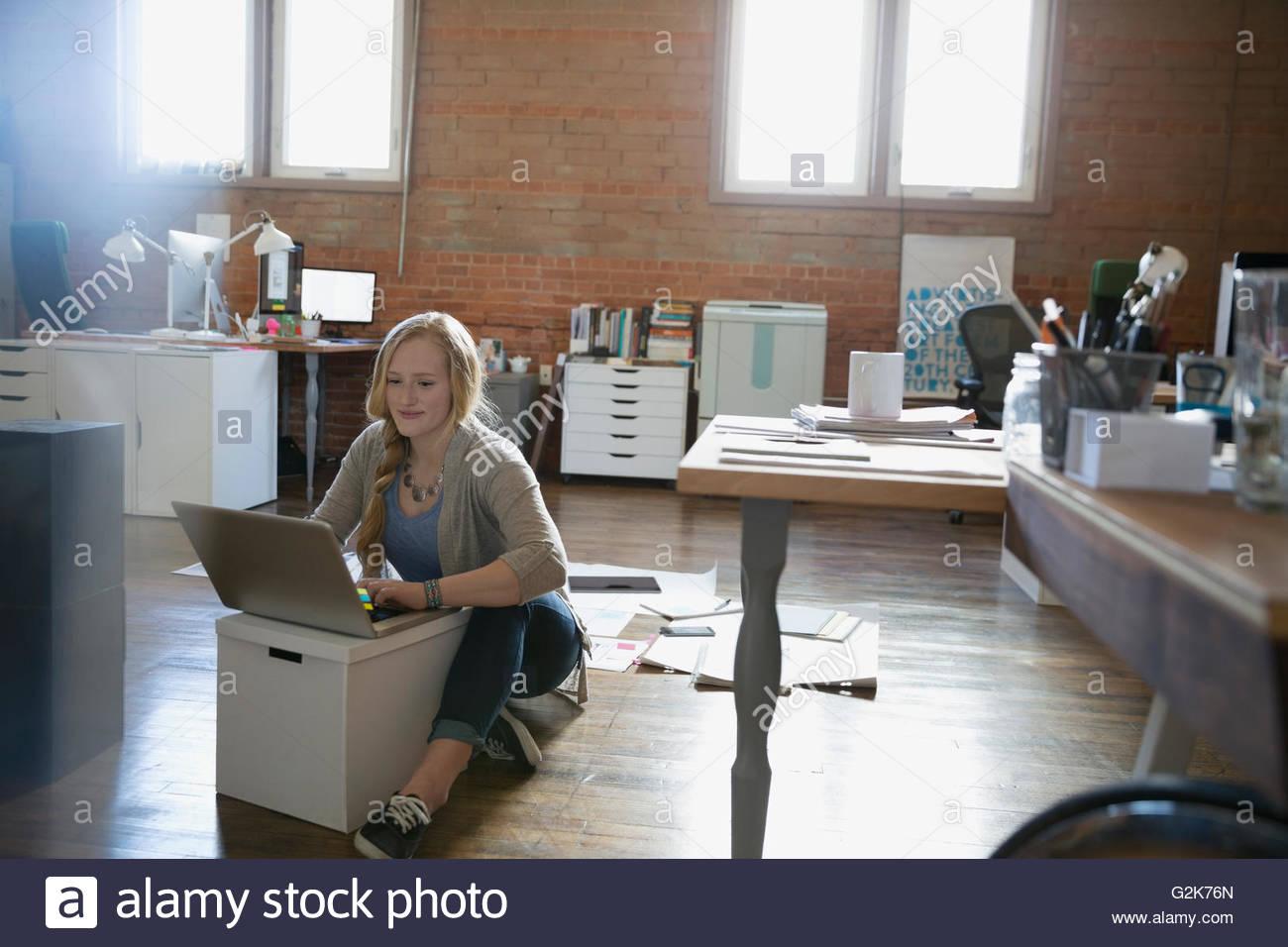 Designer femmina utilizzando laptop sul pavimento in ufficio Immagini Stock