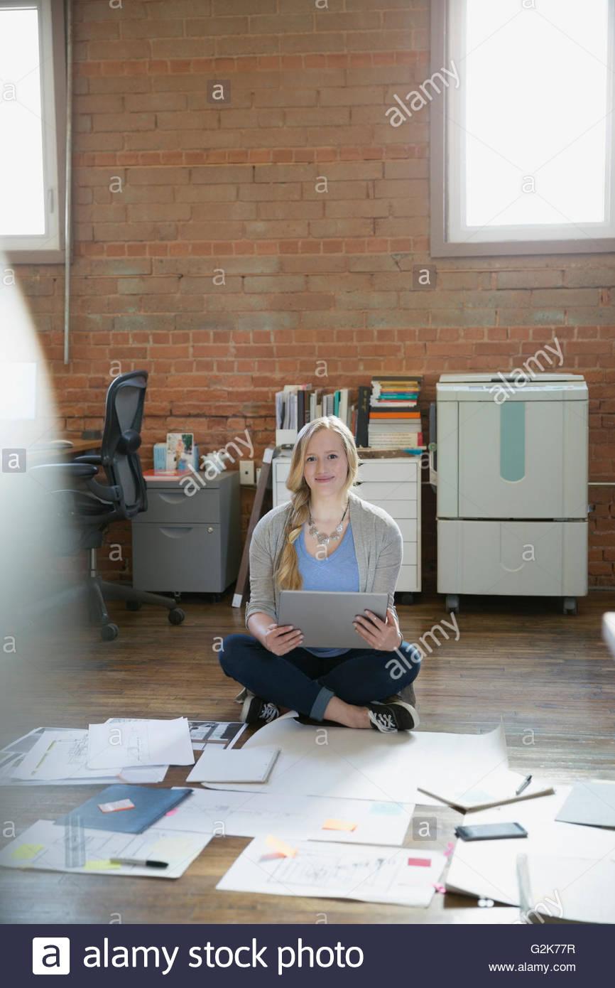 Ritratto designer femmina con tavoletta digitale su office piano con le prove e documentazione Immagini Stock