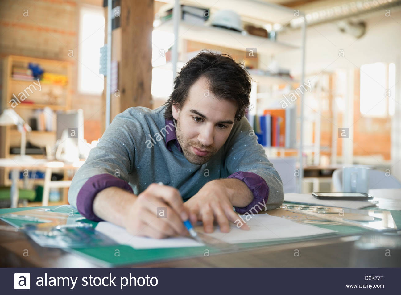 Designer con un righello e bradawl lama sul tappeto di taglio in office Immagini Stock