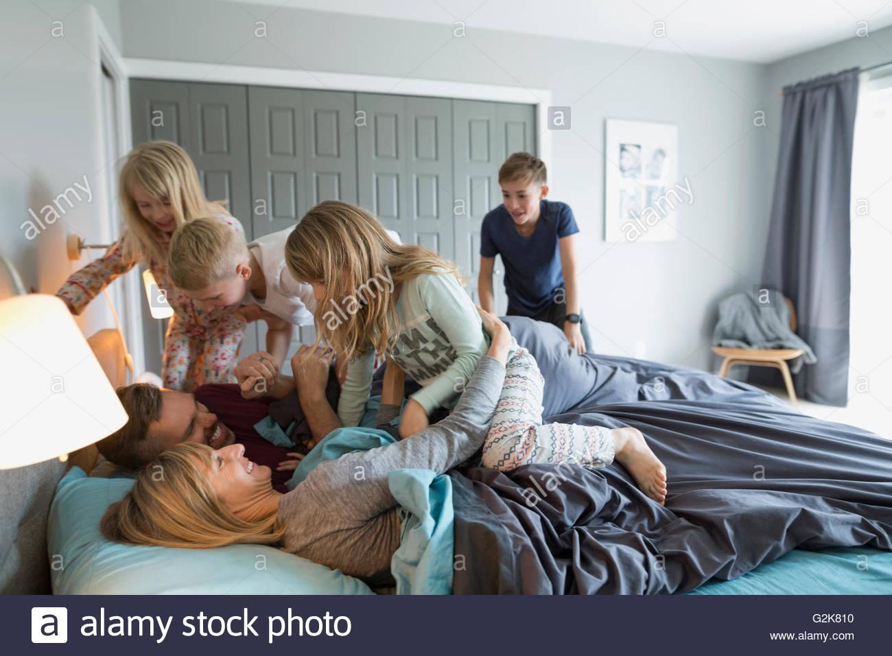 Bambini allegri in pigiama affrontare i genitori nel letto Immagini Stock