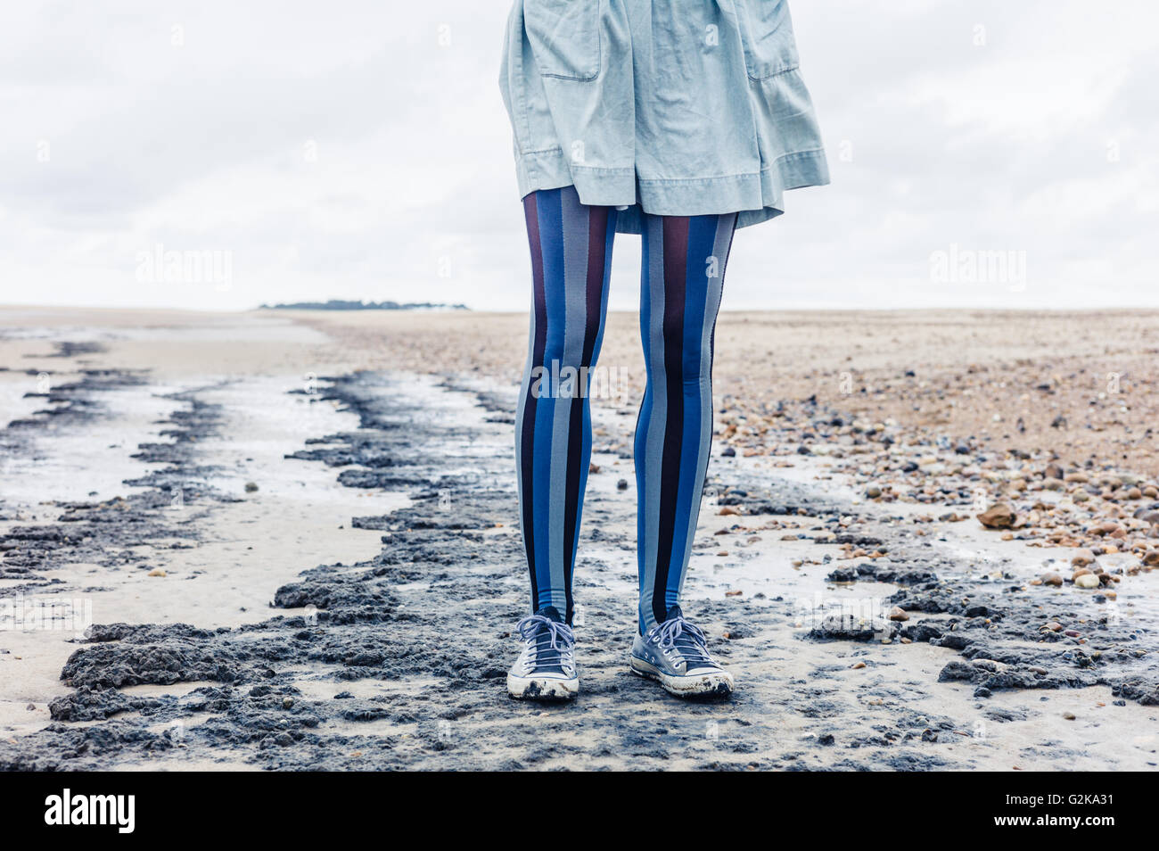 Le gambe di una giovane donna come lei è in piedi sulla spiaggia con il suo mantello al vento Immagini Stock