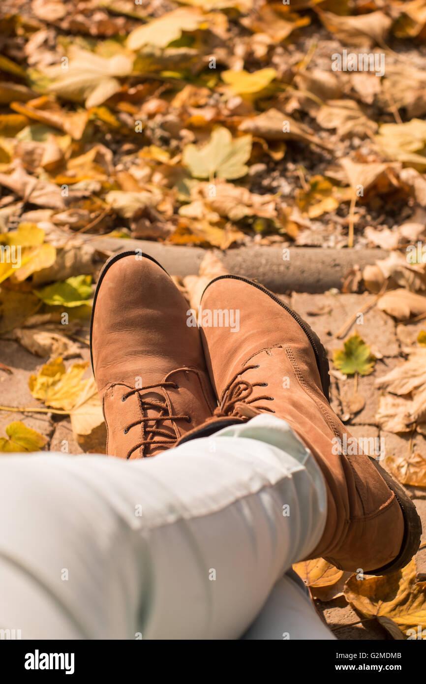 Piedi delle donne stivali andare sul parco In autunno e calcio gialli foglie cadute