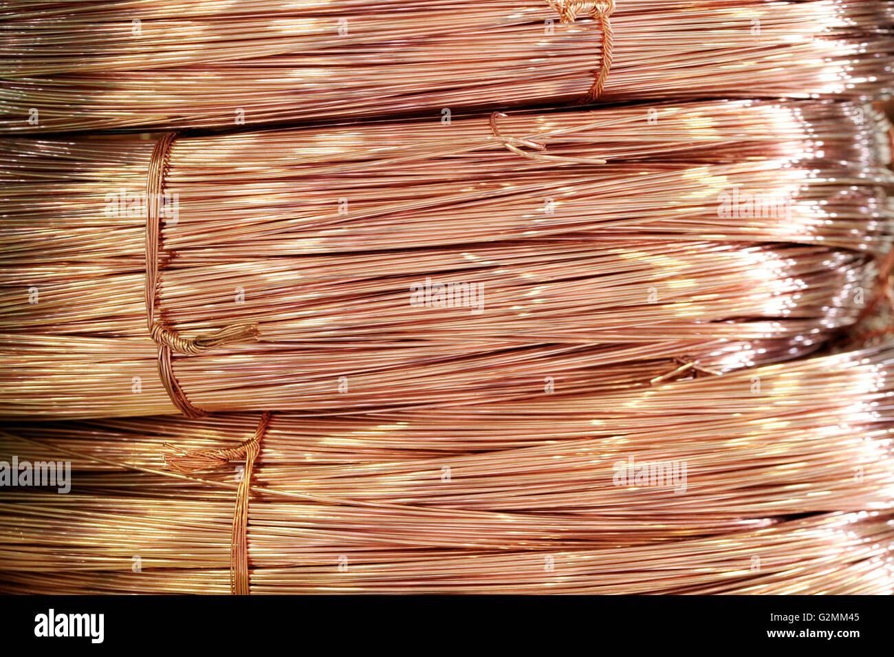 Close up sulle bobine di lucido di filo di rame memorizzate come materia prima di alimentazione in metallo per uso Immagini Stock