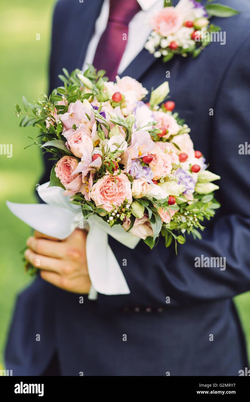 Lo sposo holding bouquet di rose, close up Immagini Stock