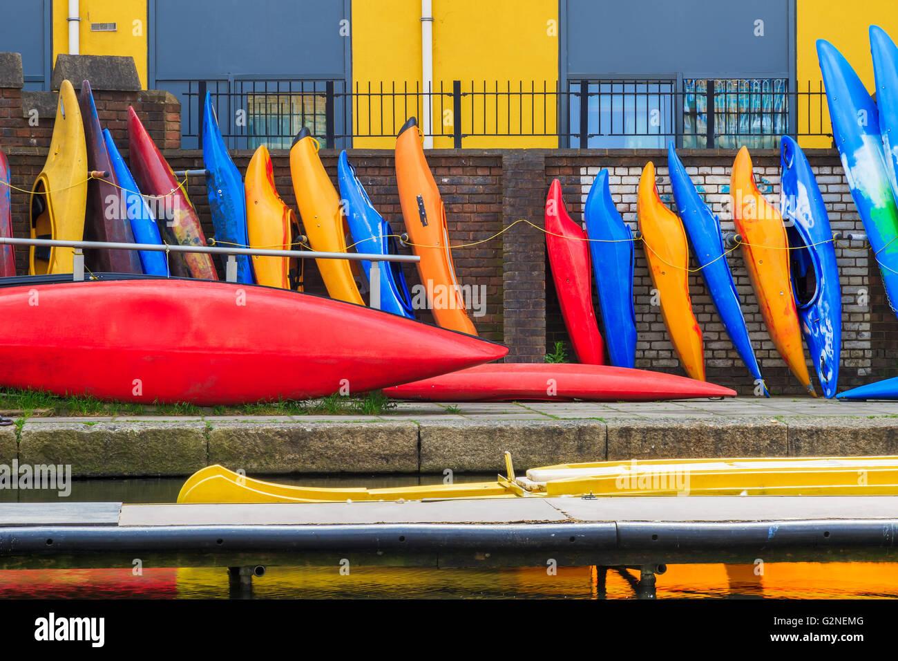 Fila di kayaks colorati appoggiati contro un muro di mattoni sul Regent's Canal a Londra Immagini Stock
