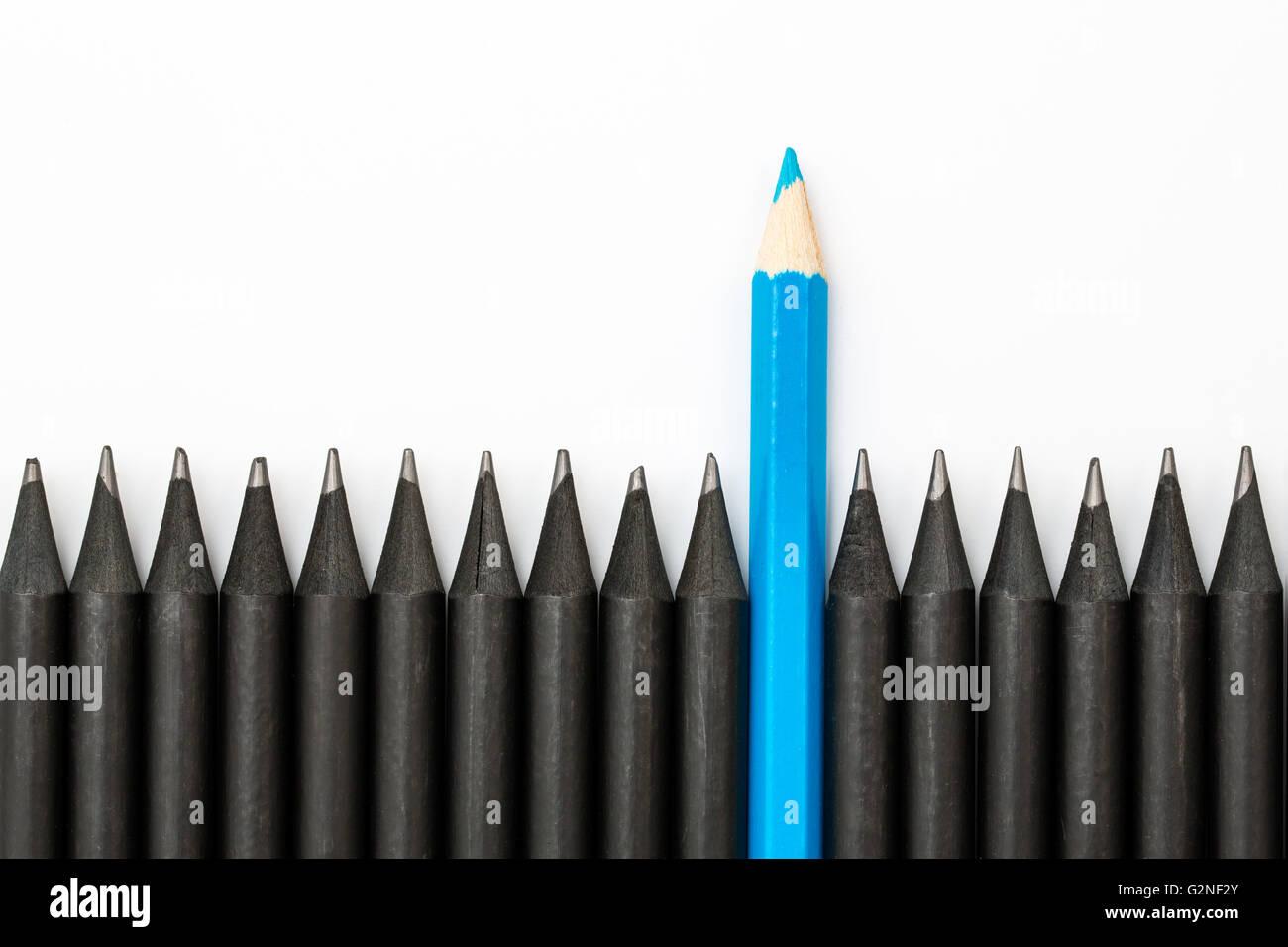 Matita blu in piedi fuori dalla fila di matite di colore nero. Immagini Stock