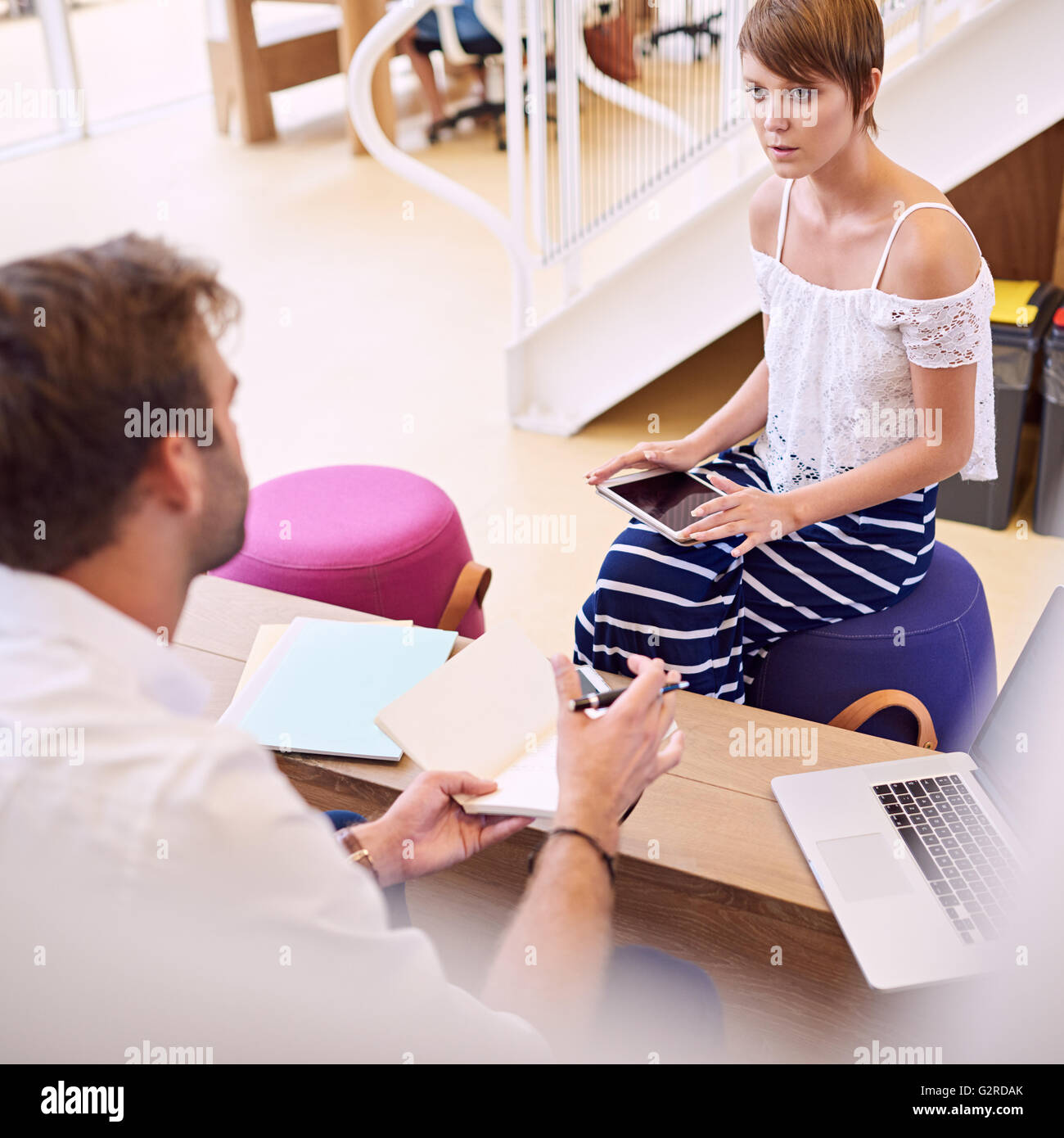 Imprenditrice prestando attenzione al suo consulente maschio mantenendo compressa Immagini Stock