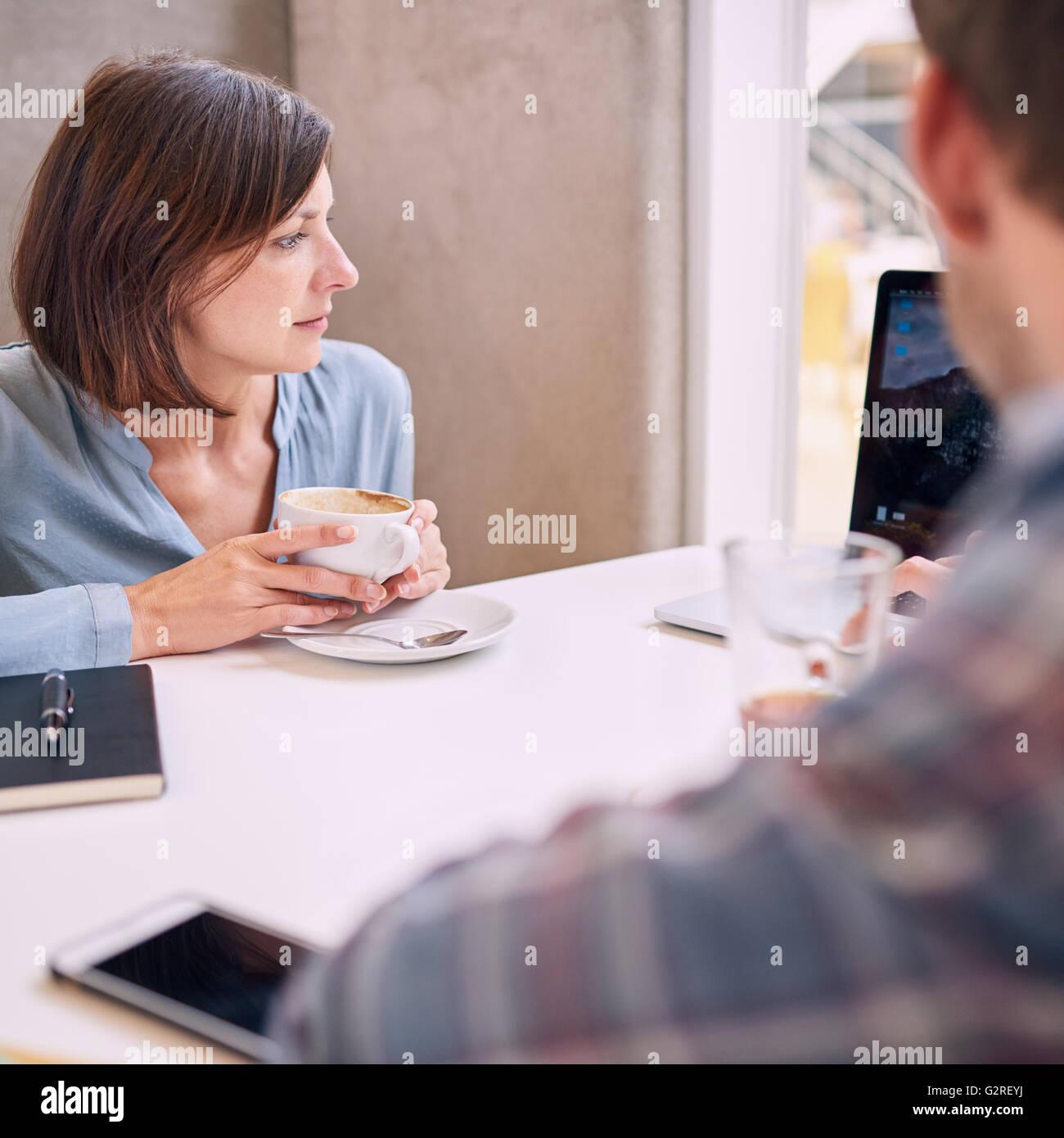 Stretto colpo di donna che guarda al laptop tramite mans spallamento Immagini Stock