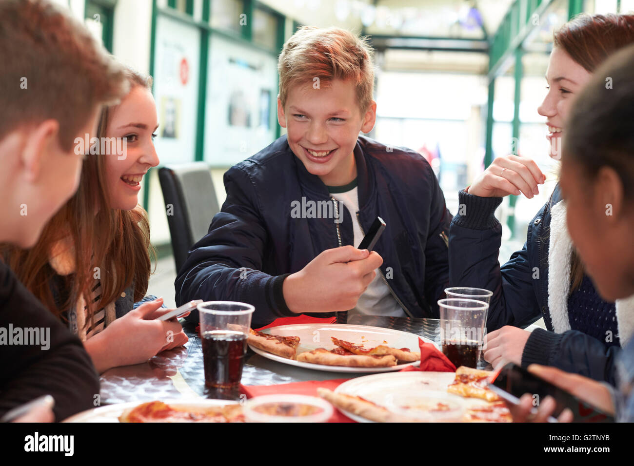 Gli adolescenti di mangiare la pizza in Cafe e guardando il Telefono Cellulare Immagini Stock