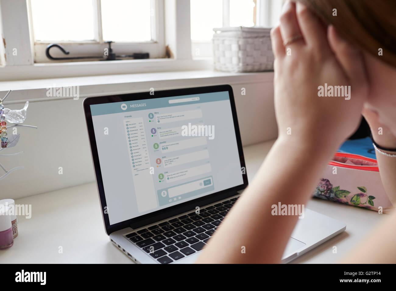 Adolescente infelice vittima di bullismo online in camera da letto Immagini Stock