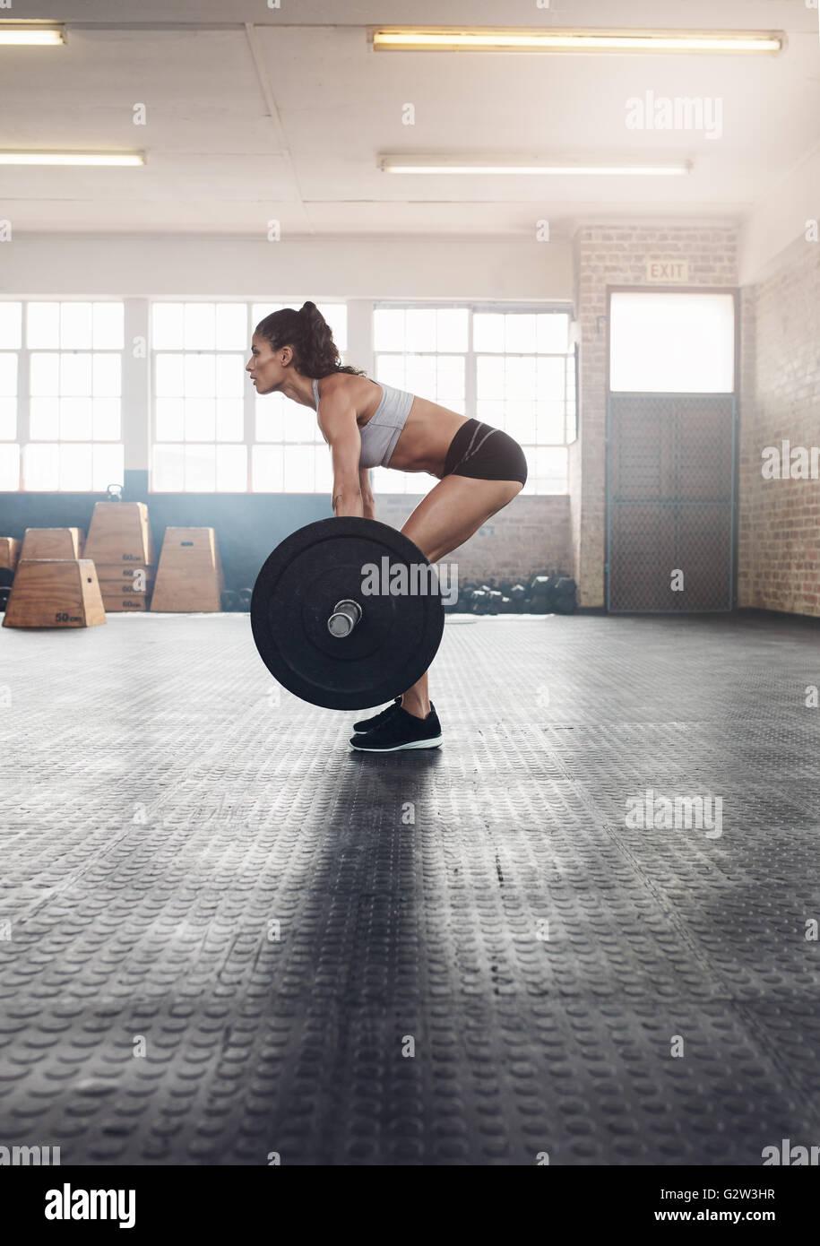 Vista laterale della donna fitness ginnastica con pesi pesanti in palestra. Donna muscolare praticare il sollevamento Immagini Stock