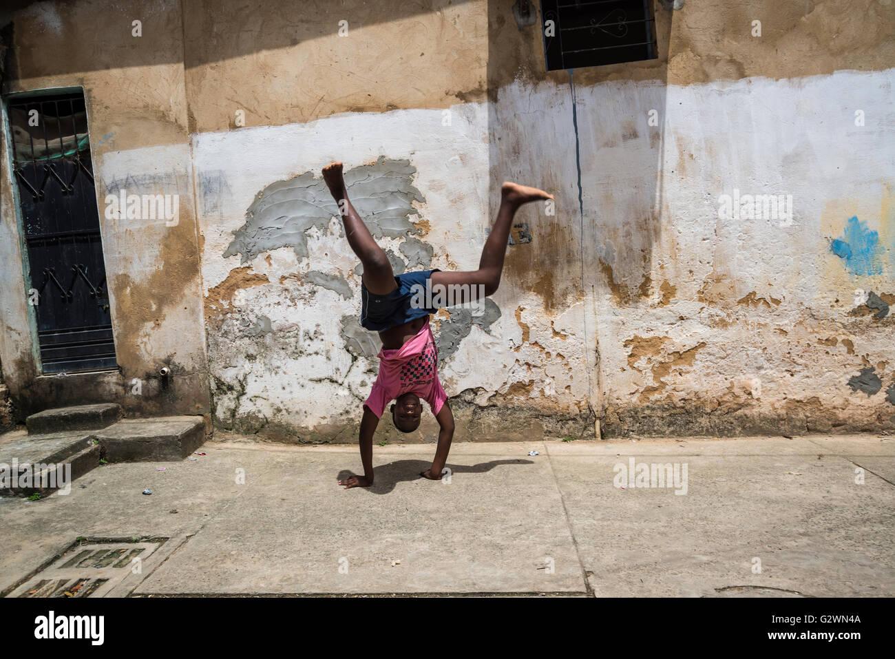 Il ragazzo, Salvador, Bahia, Brasile, handstand, favela, povertà, giocando, singolo Immagini Stock