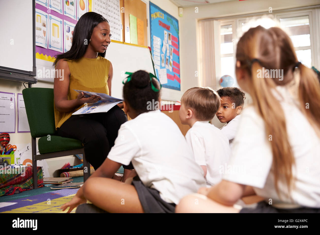 Lettura di insegnante di scuola elementare gli alunni in aula Immagini Stock