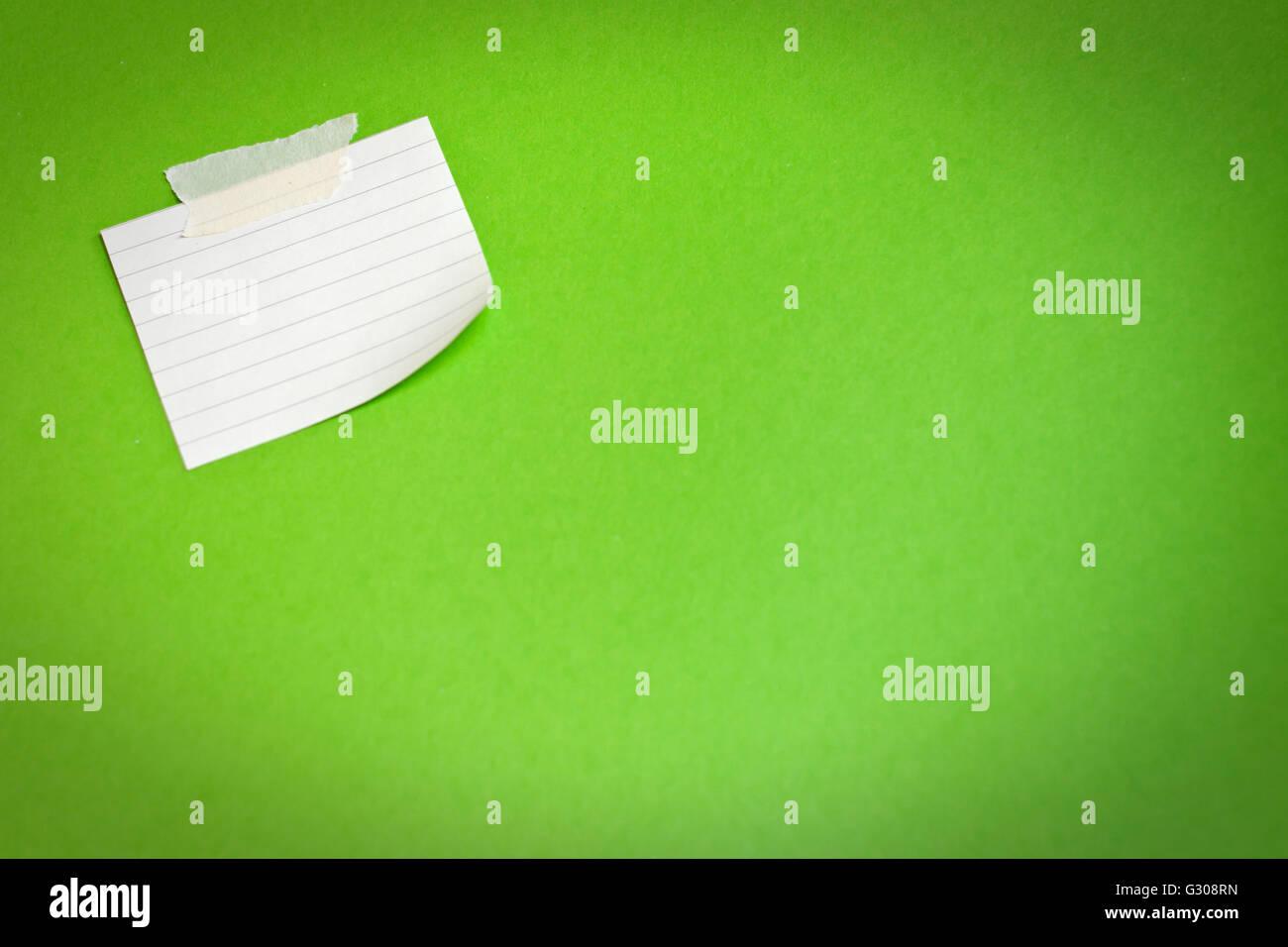 Nota bianco carta attaccata su sfondo verde Immagini Stock
