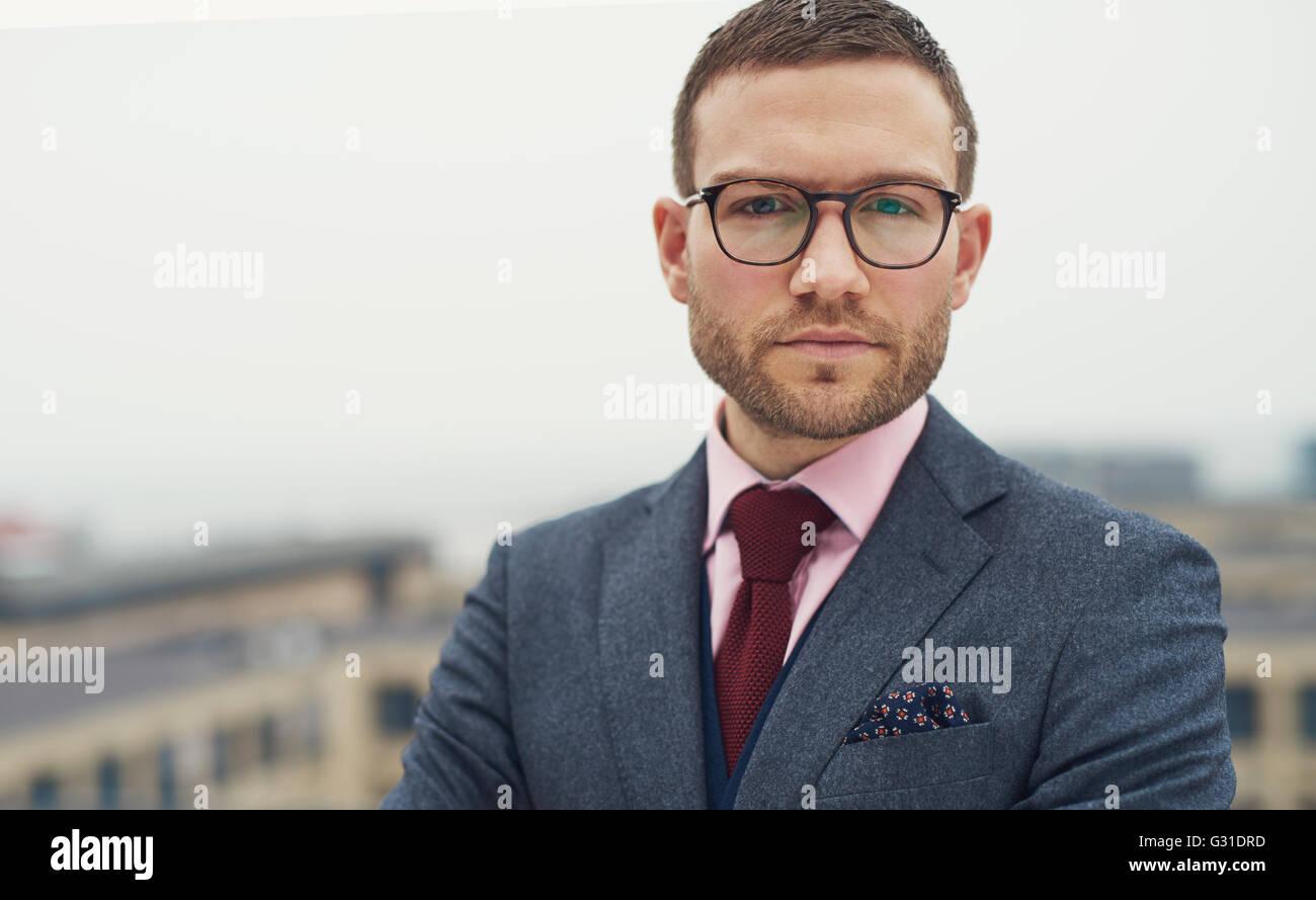 Grave intenso giovane imprenditore con bicchieri in piedi all'aperto su un open-air balcone fissando la telecamera, Immagini Stock