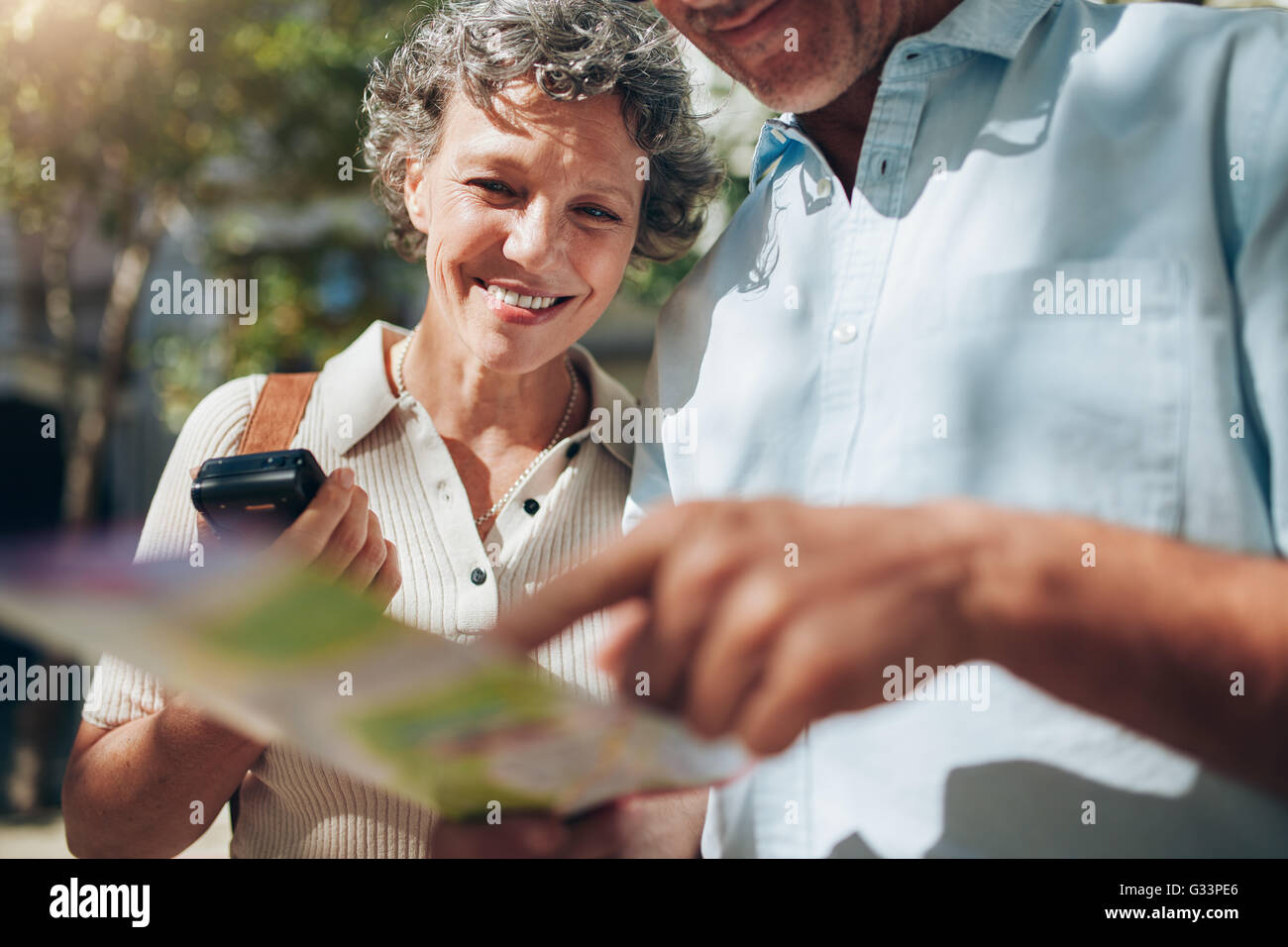Coppia di mezza età guardando la mappa della città. Felice donna matura con suo marito in una vacanza Immagini Stock