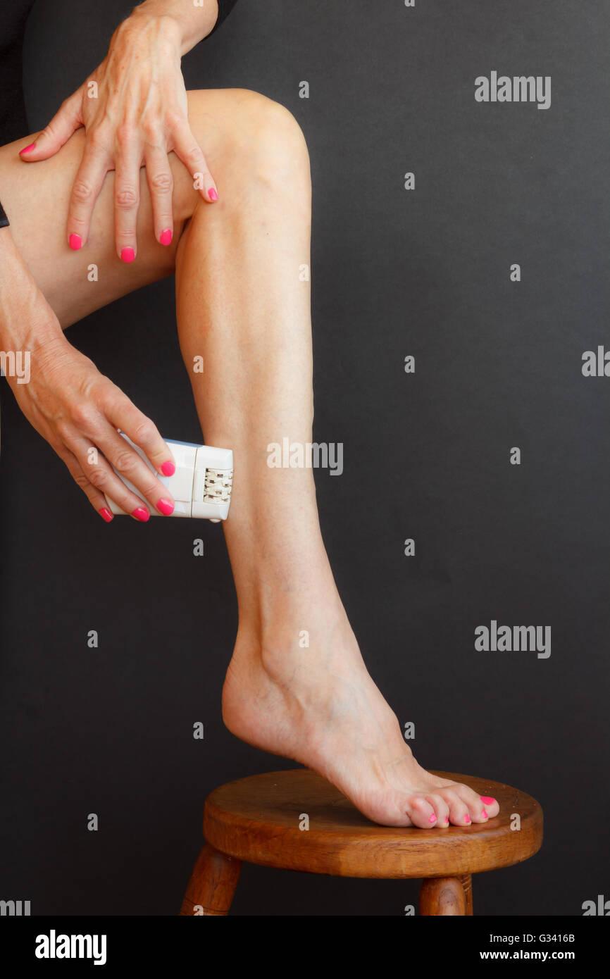 Una donna la rasatura le gambe tirando la pelle con le mani e mettere il piede sullo sgabello Immagini Stock