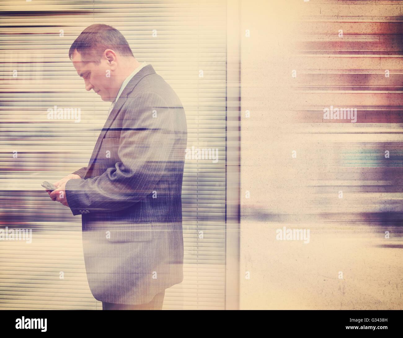 Un uomo di affari di un abito è sms sul suo telefono cellulare nella città fuori con una parete per una Immagini Stock