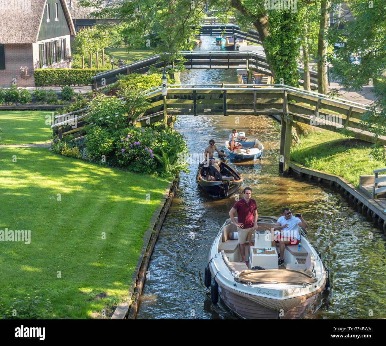Giethoorn, Paesi Bassi. Barche in Dorpsgracht o canale di villaggio con case coloniche convertito su isole con ponti di privato. Foto Stock