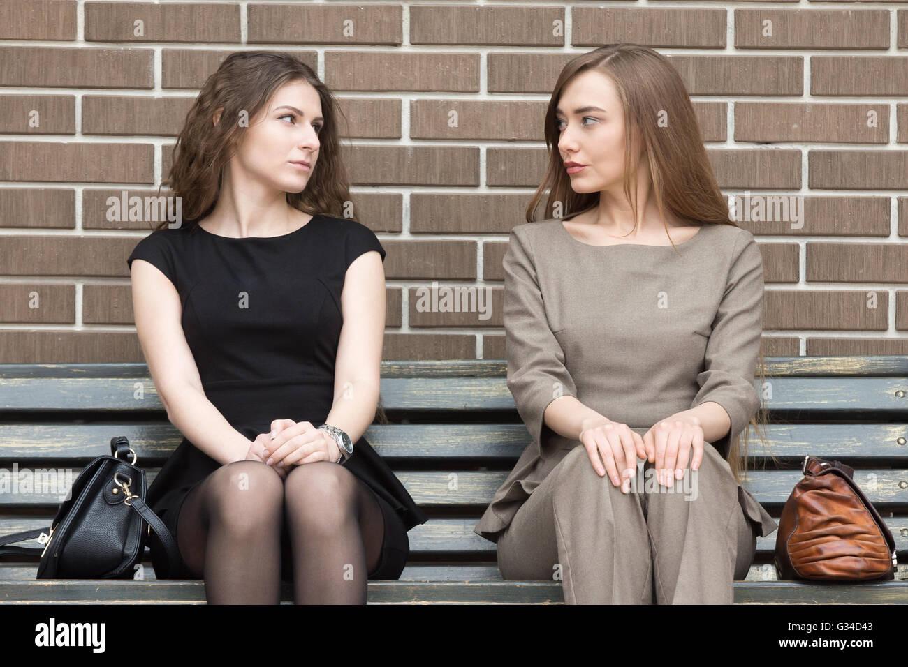 Ritratto di due belle giovani femmine rivali seduti fianco a fianco sul banco e guardando ogni altra con impegnativo Immagini Stock