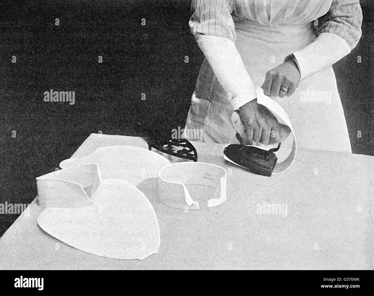 Fotografia che mostra la tecnica per la stiratura di bib e collari in 1911. Data: 1911 Immagini Stock