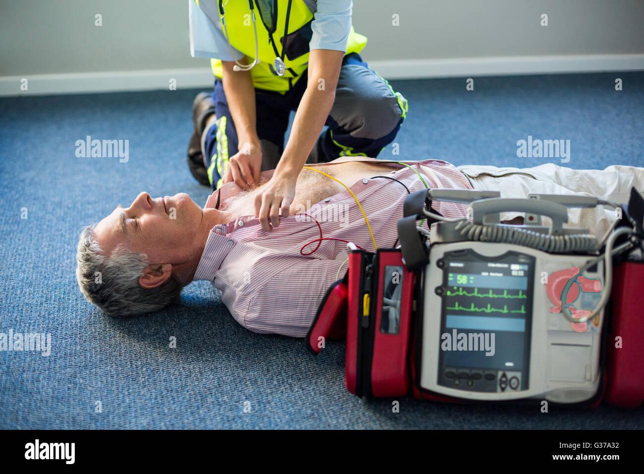 Paramedic utilizzando un defibrillatore esterno su un paziente in stato di incoscienza Immagini Stock