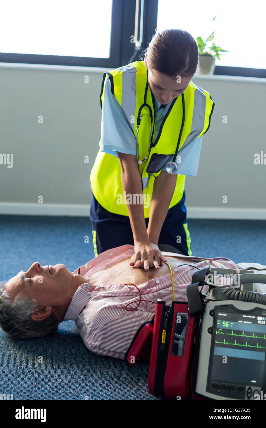 Paramedic utilizzando un defibrillatore esterno durante la rianimazione cardiopolmonare Foto Stock