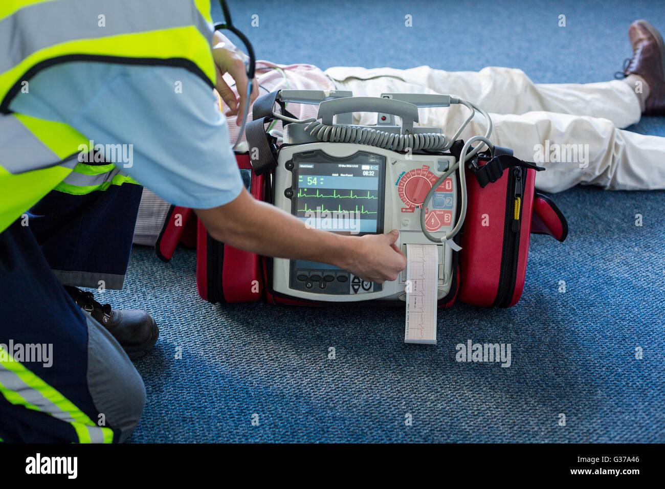 Paramedic utilizzando un defibrillatore esterno durante la rianimazione cardiopolmonare Immagini Stock