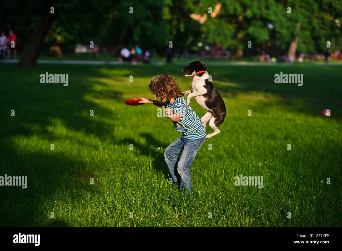 Il ragazzo treni un cane.In un giardino estivo del ragazzo di 8-9 anni suona con un cane.In una mano al ragazzo Immagini Stock
