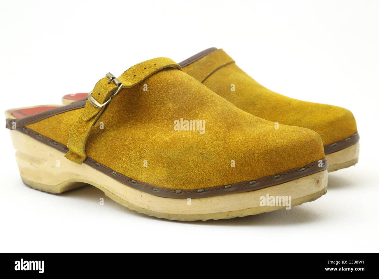 Una coppia di giallo senape Suede zoccoli Immagini Stock