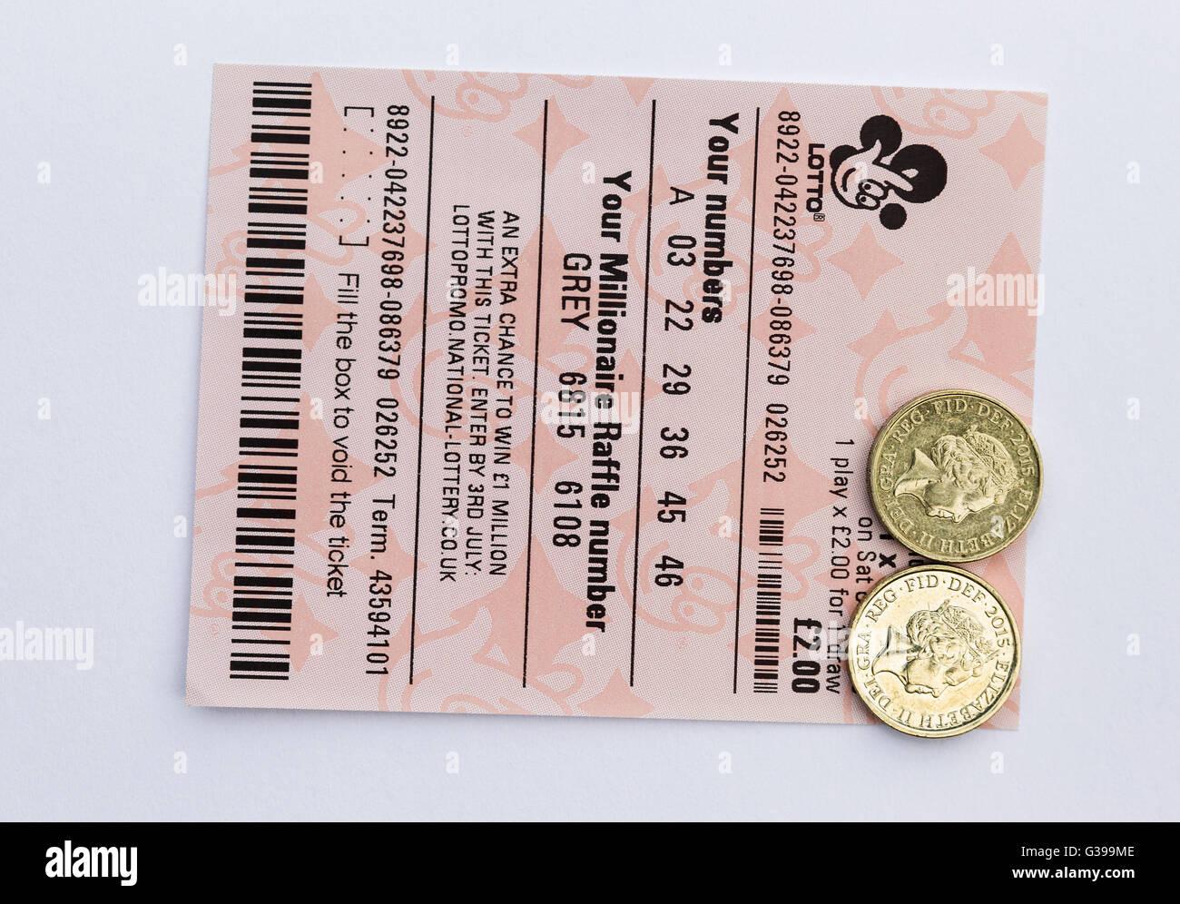 Un due pound UK Lotto ticket con due libbre di monete. Immagini Stock