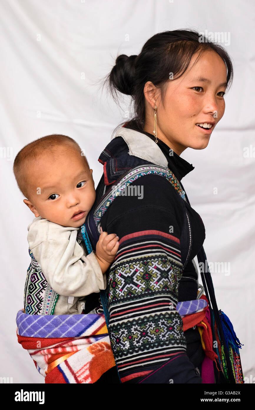 Una donna Hmong e baby, indossando il costume tradizionale di Sapa, Lao Cai Provincia, Vietnam Foto Stock