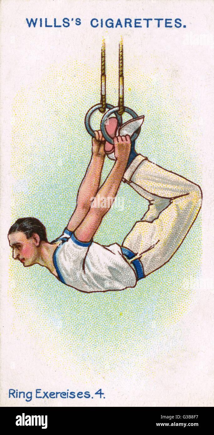 Un ginnasta maschio pende da anelli dalle sue mani e piedi. Data: 1914 Immagini Stock
