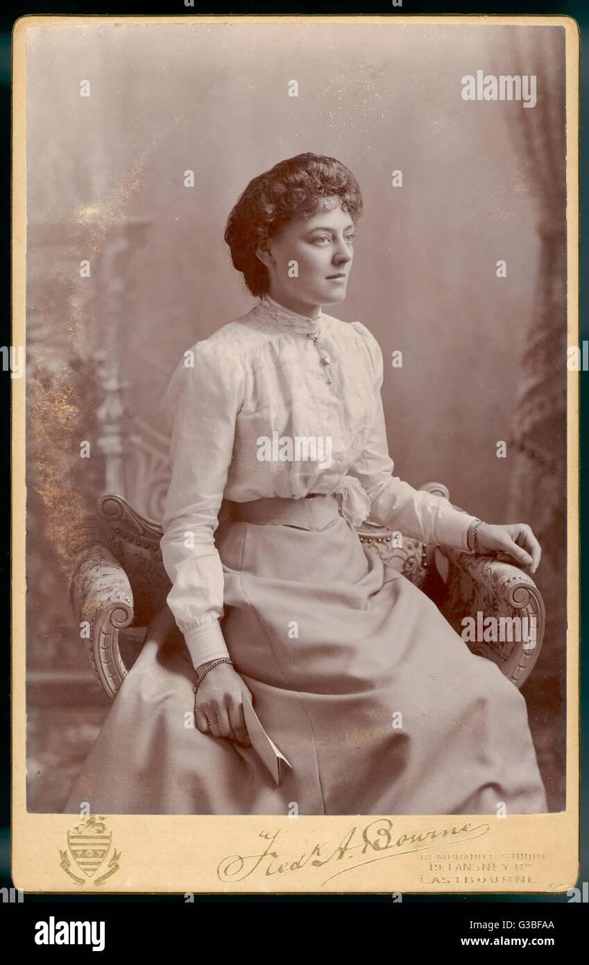 Una giovane donna indossa un semplice mantello gored & una camicetta rifinito con pizzo con un colletto Immagini Stock