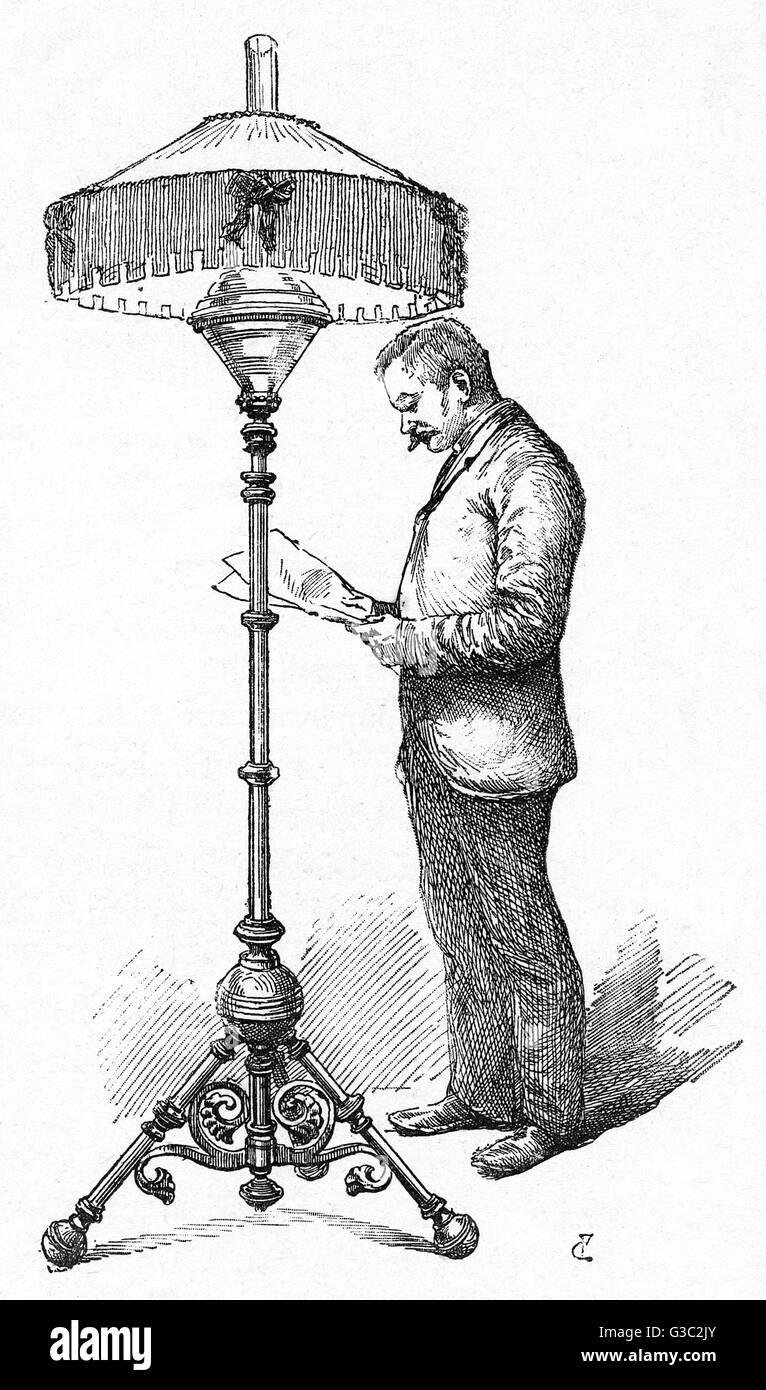 Un uomo legge al di sotto della luce di un Hink olio della lampada. Immagini Stock