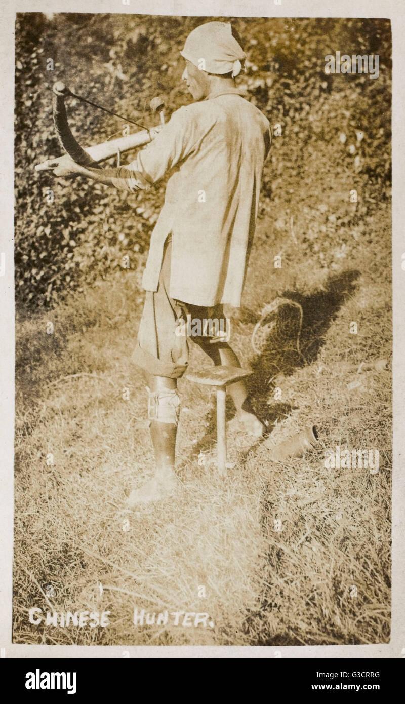 Il cacciatore cinesi armati con una balestra Data: 1920s Immagini Stock