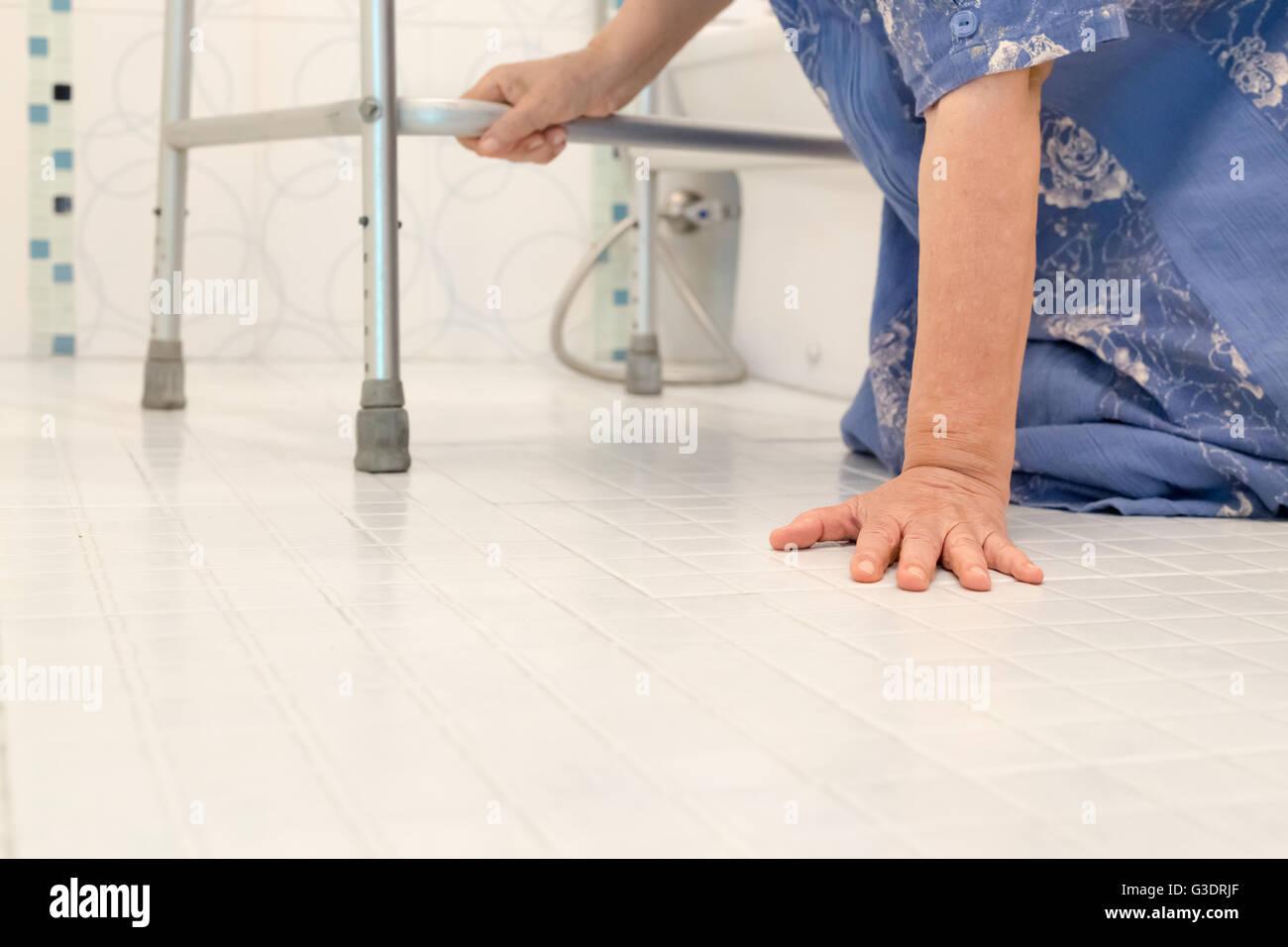 Donna anziana caduta in bagno a causa di superfici scivolose Foto Stock