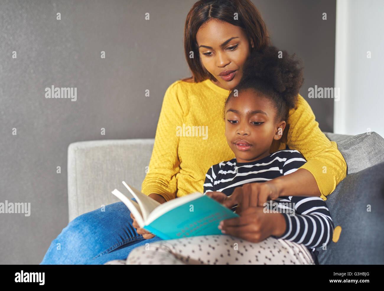 Mamma e figlia leggendo un libro cercando di lettura eccitato Immagini Stock